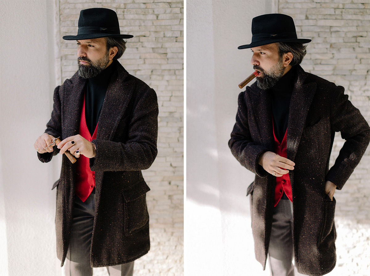 man and wearing coat, red vest and fedora hat smoking cigar