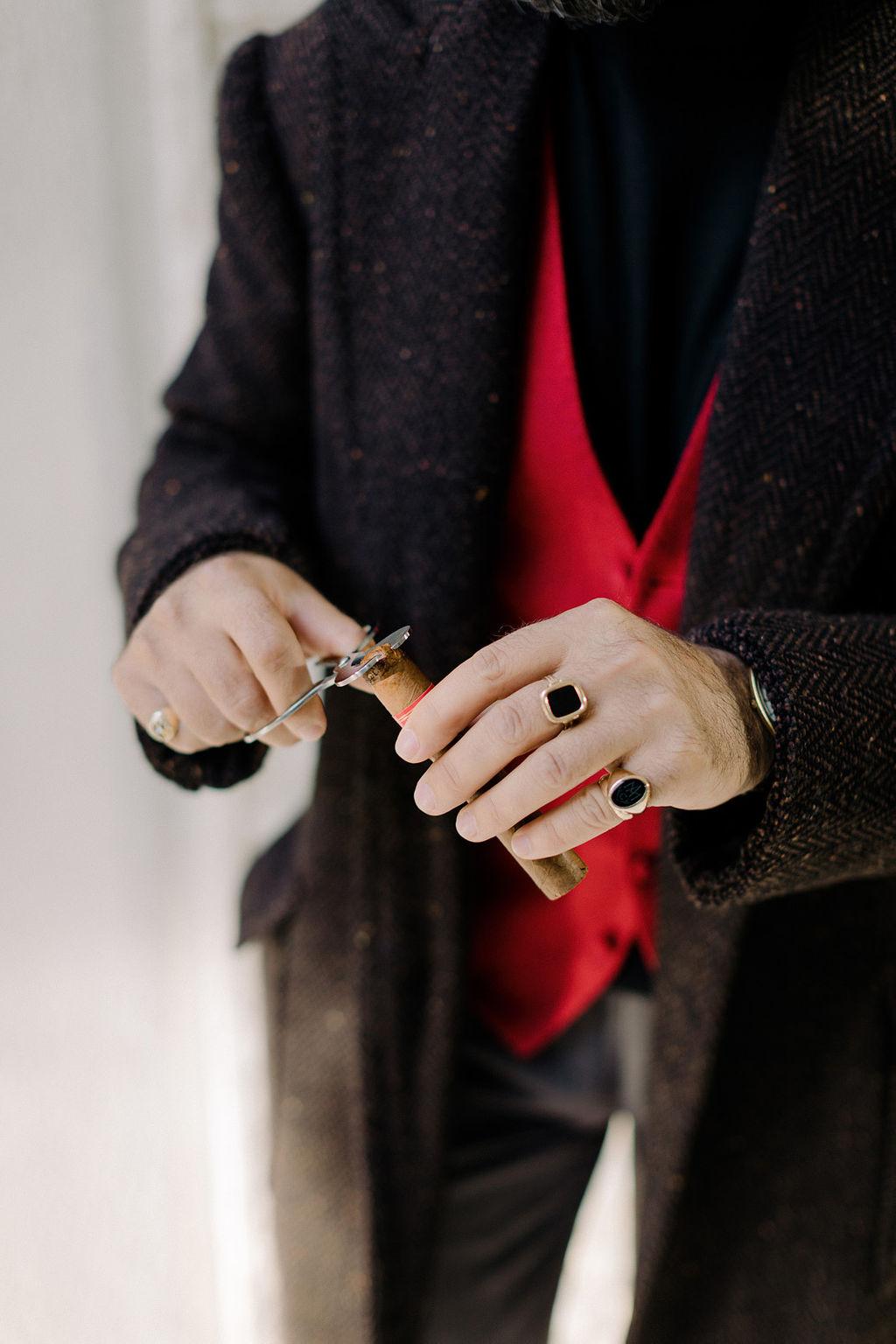 Man wearing gold signet ring cutting cigar