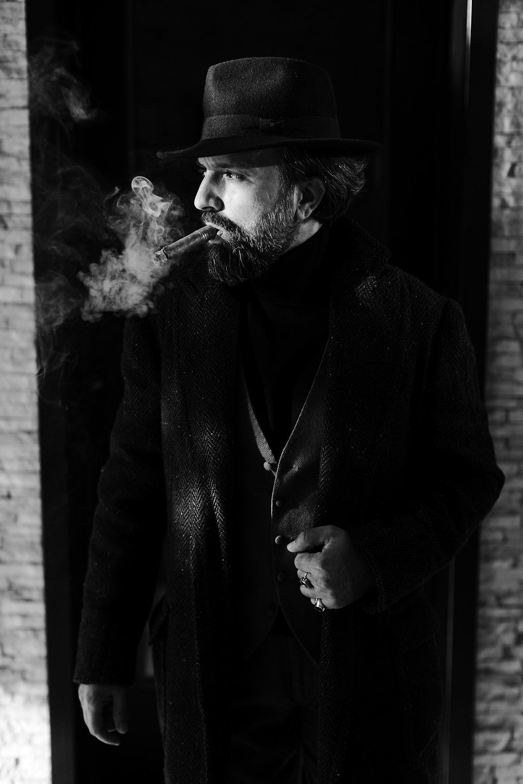 man and wearing coat, red vest and fedora hat smoking cigar street style