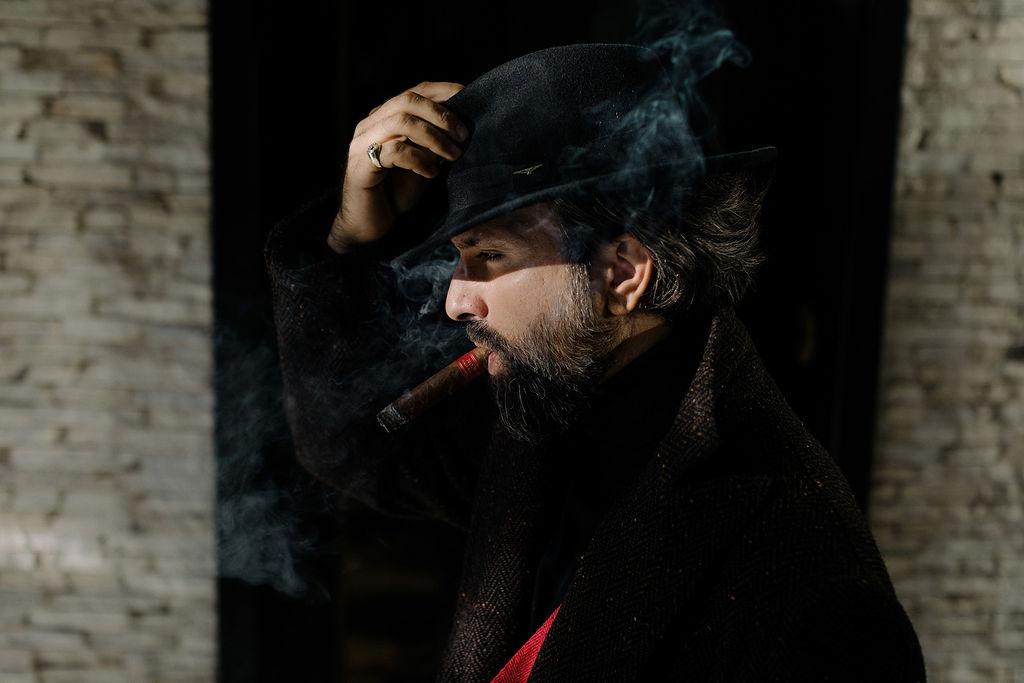 Man with fedora hat smoking cigar