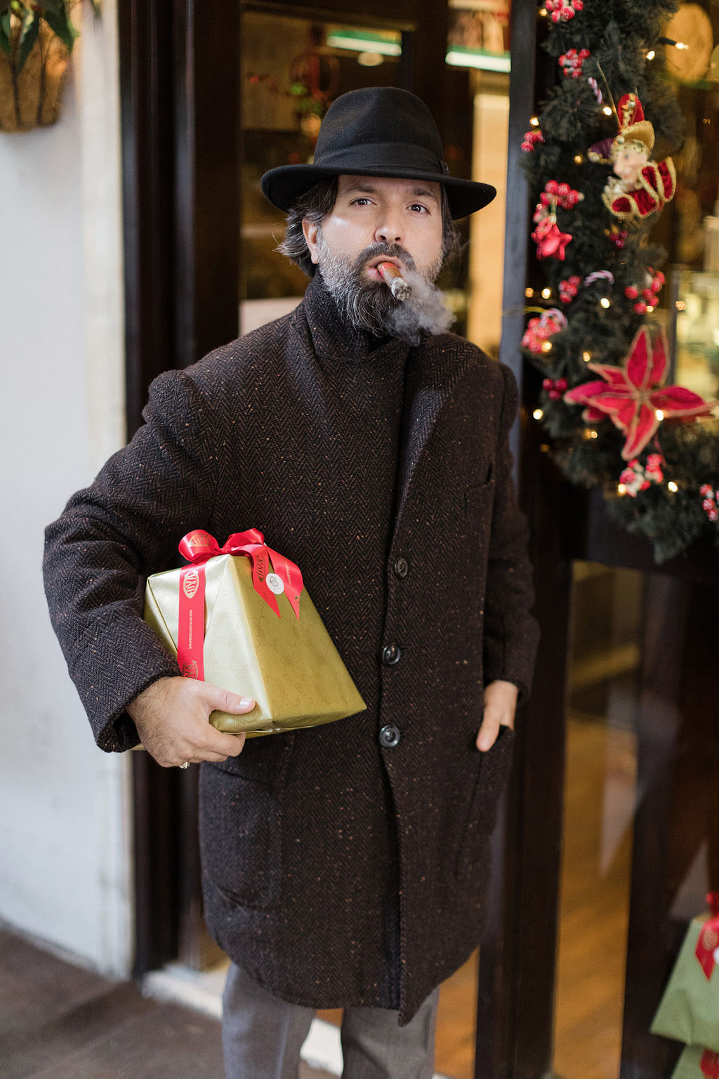Christmas shopping man holding panettone and wearing coat and fedora hat smoking cigar