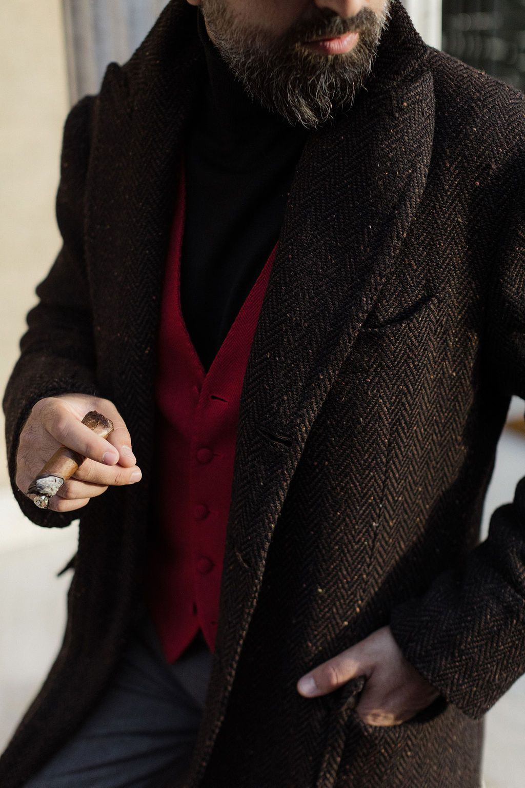 man and wearing coat and red vest and fedora hat smoking cigar